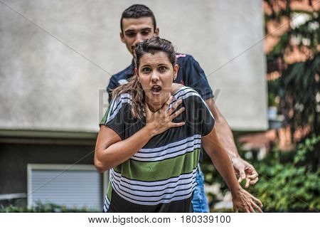 young guy helping a young girl while she's choking