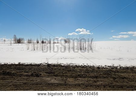 Snowfield with a thawed patch in the form of a strip