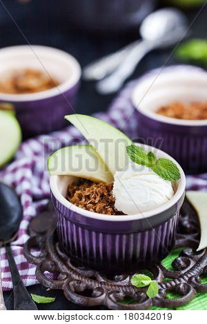 Apple crumble crisp dessert with vanilla ice cream on dark