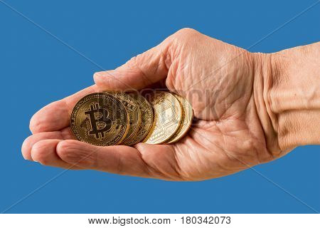 Isolated stack of bit coins or bitcoin held in man's hand on blue background to illustrate blockchain and cyber currency