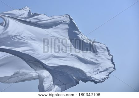 White grey flag or fabric waving in air on wind in cloudless sky on sunny day outdoors on blue background