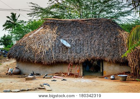 Traditional thatch hut with satellite TV dish, India