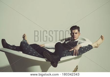 Handsome man or businessman with stylish haircut hair in fashion business wear vest tie shirt and pants relaxing with female legs barefoot in classic bath white tub on grey background