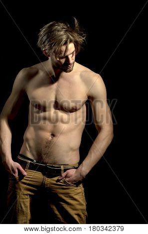 Handsome man or unshaven macho bodybuilder with stylish blond hair haircut showing sexy naked muscular torso with six packs and abs biceps triceps on black background poster