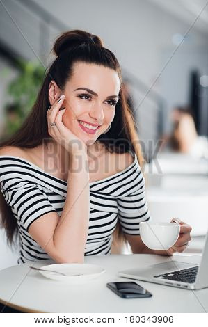 Young woman with drinking tea in a cafe. Beautiful adult woman with a cup of cappuccino at a cafe. Smiling brunette with hot beverage relaxing
