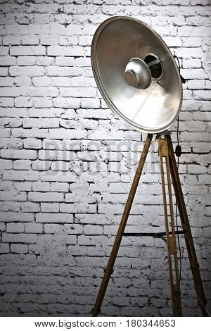 Retro studio light over the white brick wall