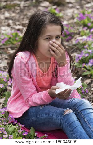 Girl has hay fever symptoms blowing her nose