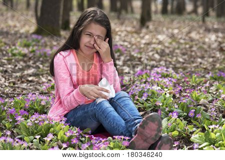 Girl sitting among primroses and rubbing her eyes
