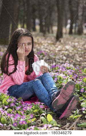 Girl holding tissue and rubbing eyes sitting on the ground