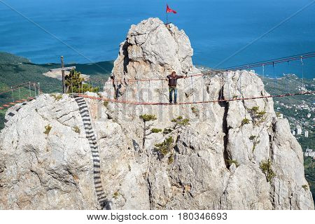CRIMEA, RUSSIA - MAY 19, 2016: Tourist walking on a rope bridge on the Mount Ai-Petri. Ai-Petri is one of the highest mountains in the Crimea and tourist attraction.