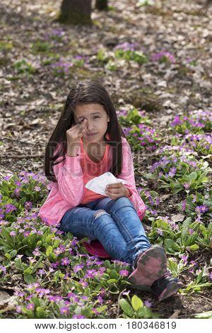 Girl with allergic rhinitis sitting among primroses