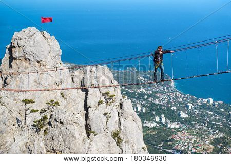 CRIMEA, RUSSIA - MAY 19, 2016: Tourist walking on a rope bridge on the Mount Ai-Petri. It is one of the highest mountains in the Crimea and tourist attraction.