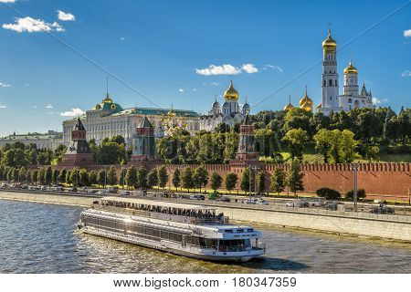 Tourist boat floats on the Moskva River past the Moscow Kremlin, Russia