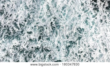 Aerial view of the foam spray and turquoise sea water. View from above of the ocean.