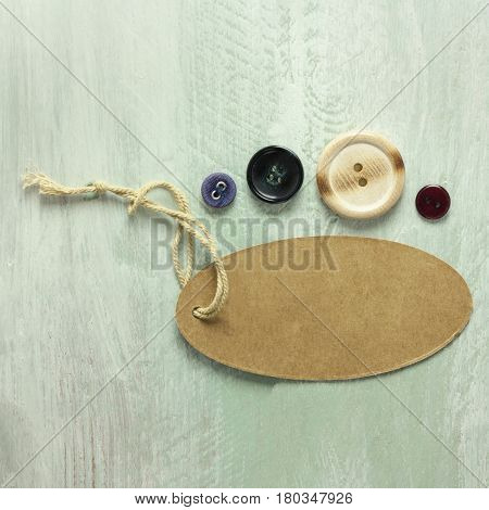A square photo of a kraft cardboard tag with a piece of twine, with retro buttons, shot from above on a light wooden board texture, with copy space