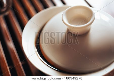 Chinese teacup or Gaiwan with black puerh tea on wooden tea board, Chinese Tea Ceremony, toned photo