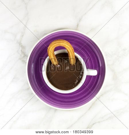 Square photo of churros, traditional Spanish dessert, particularly for Sunday breakfast, in a cup of hot chocolate, shot from above on a white marble texture with a place for text