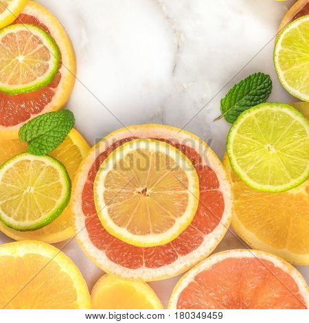 A square frame made up of juicy citrus fruits, on a white marble texture, with copy space. Grapefruit, lime, lemon, and orange slices with mint leaves