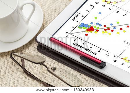 correlation scatter graph of model and observation data on a digital tablet - science or business research concept