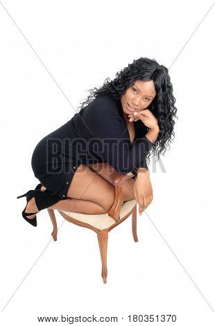 A beautiful African American kneeling on an old armchair in a black dress and high heels isolated for white background.