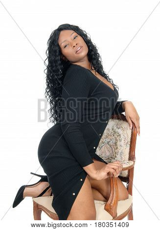 A beautiful African American business woman kneeling on an old armchair in heels isolated for white background.