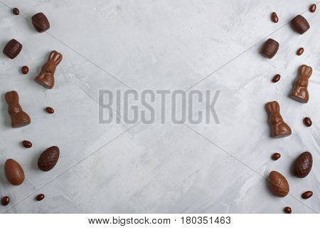 Chocolate Easter Eggs, Rabbits, Casks And Sweets On Concrete Background
