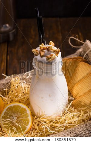 A jar with milkshake and lemon syrup, with lemon pie, cream and ice cream, with cookies