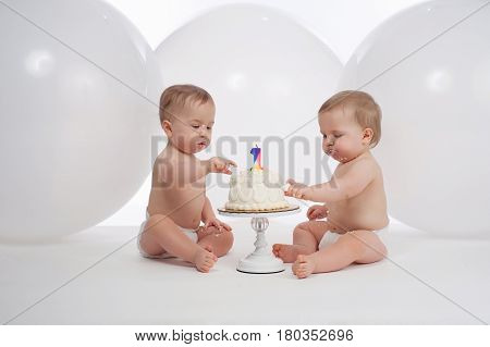 One year old twin brothers wearing diapers and eating their birthday cake. Shot in the studio with large white balloons in the background.