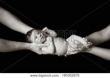 Black and white portrait of a ten day old newborn baby girl being held by her mother and father's hands. Photographed in a studio on a black background.