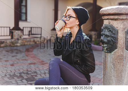Young stylishly dressed woman in black knitted hat and glasses enjoying coffee from paper take away cup. Break time concept