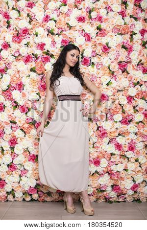 Full length portrait of a beautiful young brunette woman in a studio on a floral wall background