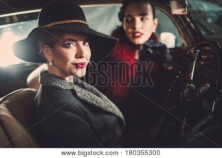 Two women among in a retro car in garage