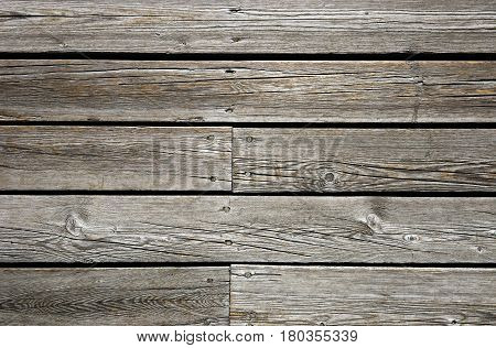 Weathered unpainted wooden fence texture with nail heads