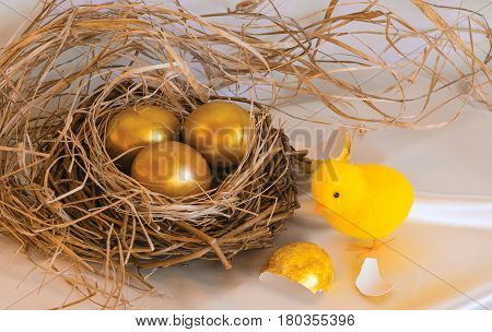 Golden Easter eggs in a bird's nest and a chicken on a silk background. Willow branches and dry grass frame the nest.