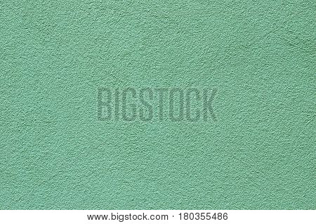 A fragment of a wall covered with green modern stucco texture Green modern stucco texture