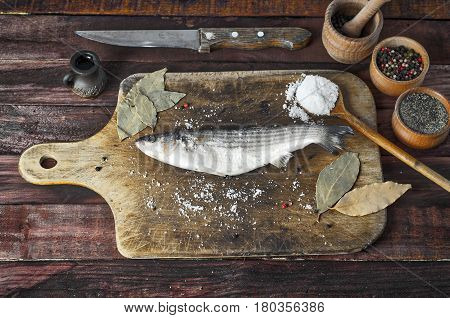 Fresh smelt fish with salt and pepper on the kitchen cutting board view from the top