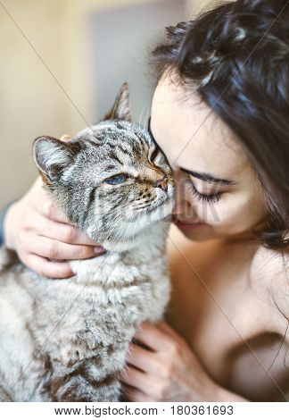 Happy beautiful young woman in the morning in bed with a cat. A woman without clothes and covered with a blanket. Morning photograph with a natural light from the window at home. Good mood and a pleasant start to the day
