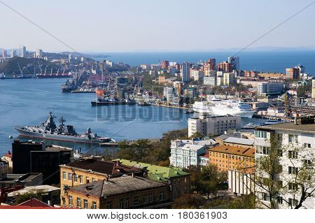 Port of Vladivostok - view from a high point at the Sea terminal, passenger ship and the rooftops of the city. Golden horn - harbor gate of Russia. Business life of the town center.