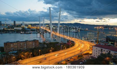 Traffic of the port city by night. Golden bridge -- cable-stayed bridge across the Zolotoy Rog Bay in Vladivostok. Was built in the framework of preparation to the APEC summit. Modern bridges Russia.