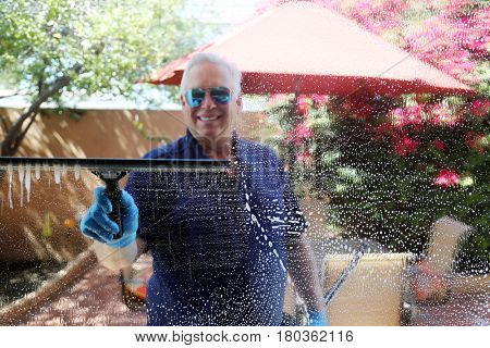 A window washer cleans windows with his squeegee and soapy water.