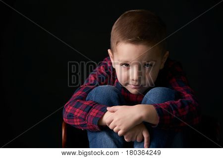 Close-up portrait of a Little brooding boy in a plaid shirt and jeans trousers sitting on the chair on isolated black background. Human emotion facial expression.