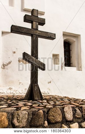 Brown cross of hardwood near the white wall of the Orthodox church.