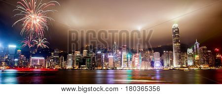 Panorama view of Hong Kong skyline with lasers floodlights and fireworks illuminating the night skies on Victoria Harbor. Viewed from downtown Tsim Sha Tsui on Hong Kong Island.