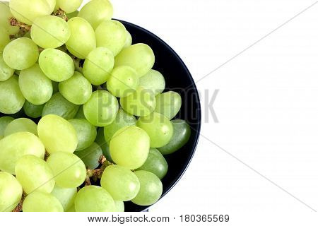 Lot of ripe green grape berries on bunche in black round bowl on white background top view close up
