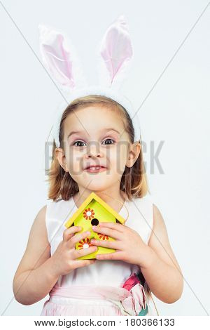 Portrait of a smiling Easter kid holding birds house