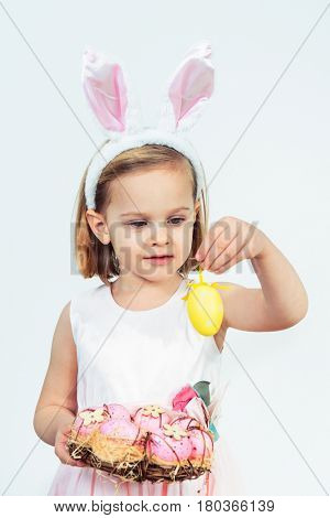Portrait of a smiling Easter kid holding egg wreath and looking at a yellow egg decoration