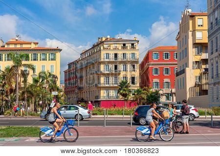 NICE, FRANCE - SEPTEMBER 04, 2016: People on rental city bicycles ride on Promenade des Anglais in Nice - city located on French Riviera, fifth most populous and one of most visited in France.