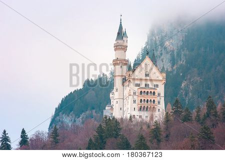 World-famous tourist attraction in the Bavarian Alps, fairytale Neuschwanstein or New Swanstone Castle, the 19th century Romanesque Revival palace in the foggy day, Hohenschwangau, Bavaria, Germany