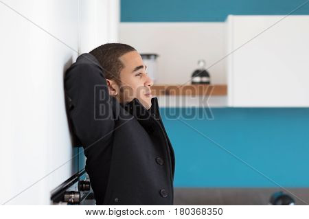 Man Relaxing In Office With Arms Behind Head