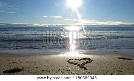 Love heart drawn in the sand of a beach. Shades of blue on an Australian beach. Horizon of a sandy beach and sunlight.